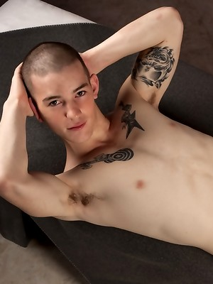 Tattooed twink Mick Gibson shows his fat cock